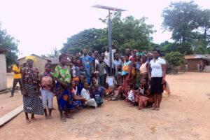Franco Dolagbenou remettant un lampadaire solaire au villageois